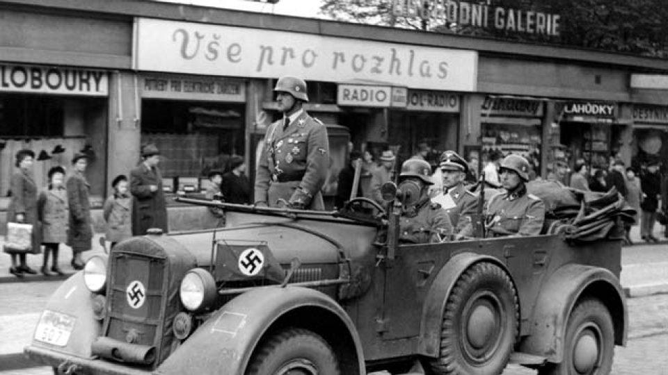 """""""Vše pro rozhlas"""": auto s policejním šéfem a říšským sekretářem protektorátu K. H. Frankem (sedící vzadu) jede kolem obchodu s rozhlasovými přijímači, po 15. březnu 1939"""