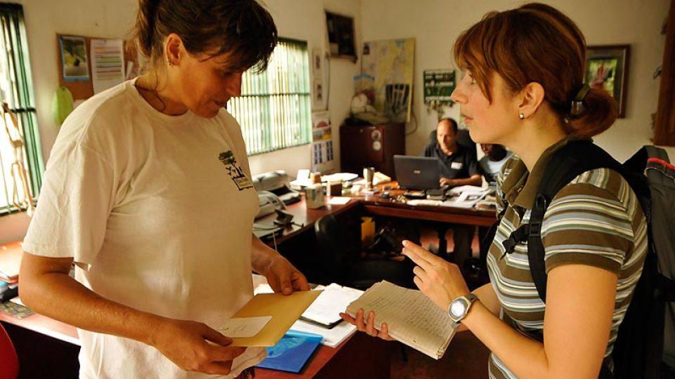 Simone de Vries dává Janě Jirátové dopisy a dotazníky, vzadu manažer LWC Felix Lankester