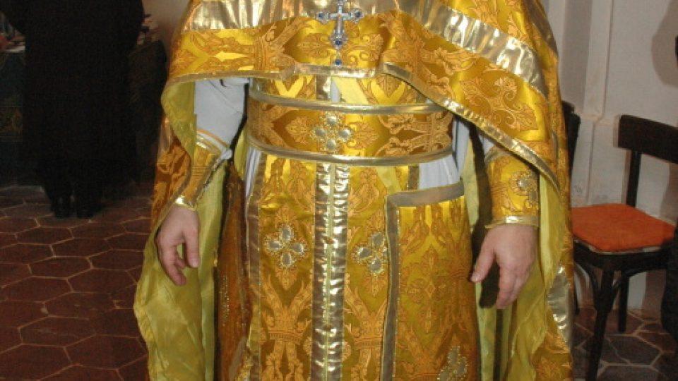 Kněz v plných liturgických rouchách zlaté barvy, pod nimi bílý stichar.