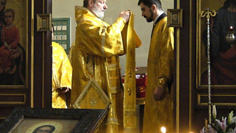 Skrze svaté dveře ikonostasu vidět biskup v plných liturgických rouchách barvy zlaté. V ruce drží epitrachil, který se chystá vložit na novosvěceného kněze. Ten má na sobě diákonský stichar a pod rukávy vidíme nárukávníky.