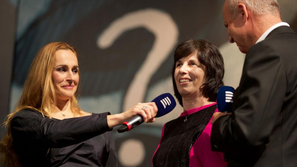 Eva Marková mezi Lucií Výbornou a Michalem Horáčkem na pódiu Koncertu pro hrdiny